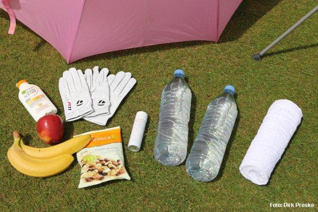 Die Utensilien für einen heißen Tag auf dem Golfplatz: Obst, z.B. Bananen und Äpfel, Nüsse, Sonnencreme, helle Handschuhe, Thermospray, viel zu trinken, Handtücher und einen Schatten spendenden Schirm. (Foto: Dirk Proske)